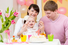 Family celebrating first birthday of baby girl. Young family celebrating first birthday of baby girl royalty free stock images