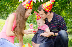 Family celebrating first birthday of their beloved daughter. In the meadow with cake, candles and cardboard colored caps stock photos