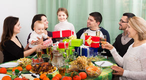 Family celebrating girl`s birthday. Relatives wishing little girl happy birthday and giving presents at festive table. Focus on girl royalty free stock image