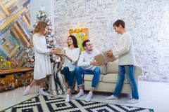 Family celebrating at home. father, mother and children on the background of the Christmas tree. New Year and xmas Stock Photos