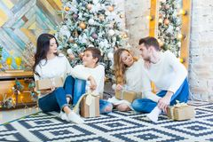 Family celebrating at home. father, mother and children on the background of the Christmas tree with presents sit on the. Carpet. New Year and xmas people Stock Photo