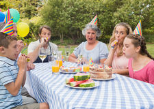 Family celebrating little girls birthday outside at picnic table Royalty Free Stock Photo