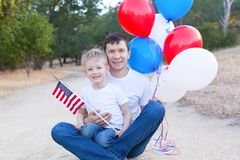 Family celebrating 4th of July. Handsome father holding colorful balloons and his little son holding american flag celebrating 4th of July Royalty Free Stock Photo