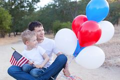 Family celebrating 4th of July. Handsome father holding colorful balloons and his little son holding american flag celebrating 4th of July Stock Photography
