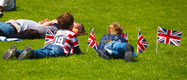Family celebrating with union jacks flying laying on the grass Royalty Free Stock Photography