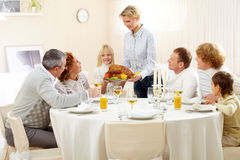 Family celebration. Portrait of big family sitting at festive table and looking at pretty woman with roasted turkey Royalty Free Stock Photo