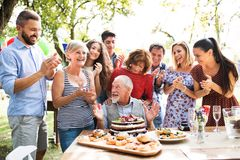Family celebration or a garden party outside in the backyard. Family celebration outside in the backyard. Big garden party. Birthday party of a senior man royalty free stock photography