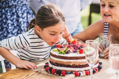 Family celebration or a garden party outside in the backyard. Family celebration outside in the backyard.Big garden party. Birthday party. Small girl with a Royalty Free Stock Image