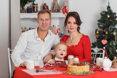 Family celebration of the New Year. The mother, father and little son in the kitchen. Holiday and fun Stock Photo