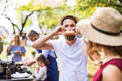 A young man eating a hamburger on a family celebration or a barbecue party outside. stock photography