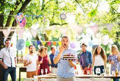 Man with a cake on a family celebration or a garden party outside, licking his finger. Family celebration outside in the backyard. Big garden or birthday party royalty free stock images