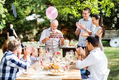 Family celebration or a garden party outside in the backyard. Family celebration outside in the backyard. Big garden party. Birthday party. A senior men holding Stock Photo