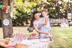 Family celebration or a garden party outside in the backyard. Family celebration outside in the backyard. Big garden party. Birthday party. Young mother with a Stock Photography