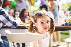 Family celebration or a garden party outside in the backyard. Family celebration outside in the backyard. Big garden party. Portrait of a small girl Stock Images