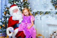 Family celebration. Santa Claus brought gifts for a cute little girl. Christmas scene. Family celebration Stock Image