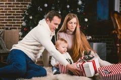 Family celebratory Christmas evening. Family three Caucasian people sitting under coniferous tree Christmas tree on floor of carpe stock image