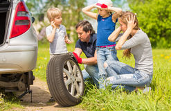 Family changes the tyre of the car. Friendly family changes the tyre of the car Stock Image