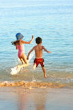 Family chase into warm sea. A brother and his sister playing chase in the warm coastal water of the mediterranean sea Stock Image