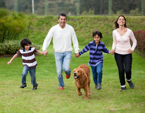 Family chasing a dog Royalty Free Stock Photo