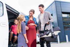 Family checking new car in car dealership Stock Photos