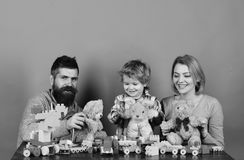 Family with cheerful faces hold teddy bears and colored construction blocks. Man with beard, woman and boy play on green. Family with cheerful faces hold teddy stock photos