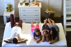 Family with cheerful and happy faces at home. Loving family and entertainment concept. Mother, father and daughters with tv remote lying on bed. Man, women and stock photo