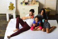 Family with cheerful and happy faces indoors. Loving family and cozy home concept. Man, women and cute children smile and hold colorful cups. Mother, father stock photos