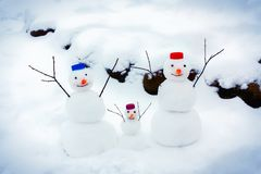 Family of cheerful snowmen rejoice at the arrival of winter and the first snow stock images