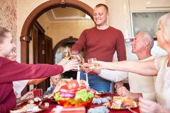 Family cheering and drinking on Thanksgiving on a blurred background. Family holiday gathering concept. Cheerful, fantastic, big family cheers glasses of wine Stock Photo