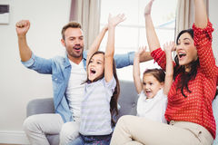 Family cheering while sitting on sofa royalty free stock photo