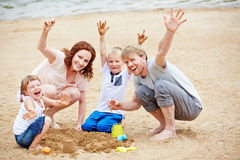 Family cheering in summer on beach Stock Image