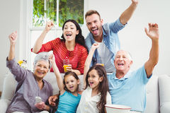 Family cheering while watching television. Happy family cheering while watching television at home Stock Image