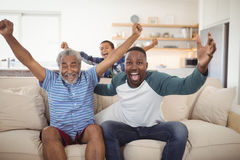 Family cheering while watching television in living room Stock Photo