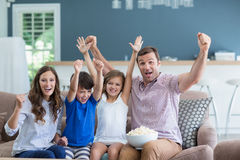 Family cheering while watching tv in living room at home Royalty Free Stock Photography