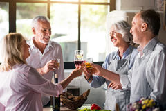 Family cheering with whiskey and wine in kitchen royalty free stock image