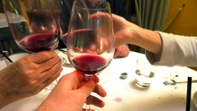 Family cheers with red wine. Close up of four hands with red wine glasses for a family cheers in a restaurant, set table on background stock video footage