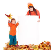 Family with child on autumn leaves holding banner. Royalty Free Stock Photo