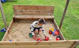 Family child boy mother playing in the sandpit in the summer. Family happy child boy mother playing in the sandpit in the summer Royalty Free Stock Image