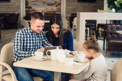 Family with child in cafe. Mother and father watching on tablet pc while girl waiting Royalty Free Stock Photos