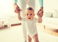 Happy baby learning to walk with mother help. Family, child, childhood and parenthood concept - happy little baby learning to walk with mother help at home stock images