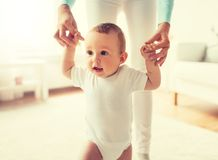 Happy baby learning to walk with mother help. Family, child, childhood and parenthood concept - happy little baby learning to walk with mother help at home stock image