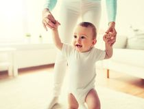 Happy baby learning to walk with mother help. Family, child, childhood and parenthood concept - happy little baby learning to walk with mother help at home stock photo