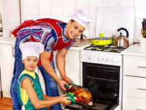 Family with child cooking chicken at kitchen. Royalty Free Stock Image