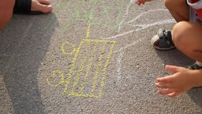 Family with child draws with chalk on the asphalt. games outdoors stock video