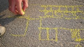 Family with child draws with chalk on the asphalt. games outdoors stock footage