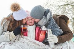 Family with child drinking tea. And cuddling in winter royalty free stock photography