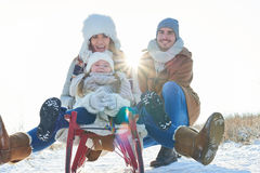 Family with child drive toboggan or sled Royalty Free Stock Photography