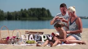 Family with child enjoying picnic on river bank stock footage