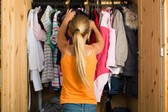 Family - child in front of her closet or wardrobe. Family - child or teenager in front of her closet or wardrobe and looking for outfit royalty free stock image