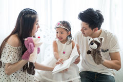 Family, child and home concept - smiling parents and little girl Royalty Free Stock Images